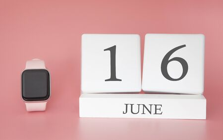 Modern Watch with cube calendar and date 16 june on pink background. Concept summer time vacation.