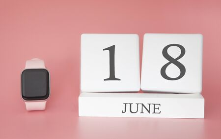 Modern Watch with cube calendar and date 18 june on pink background. Concept summer time vacation.