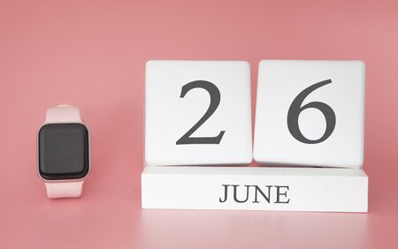 Modern Watch with cube calendar and date 26 june on pink background. Concept summer time vacation. 스톡 콘텐츠