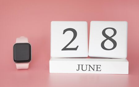 Modern Watch with cube calendar and date 28 june on pink background. Concept summer time vacation.