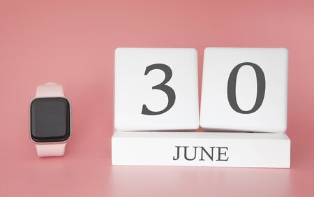 Modern Watch with cube calendar and date 30 june on pink background. Concept summer time vacation.