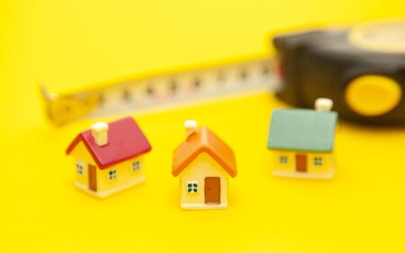 Building tape measure and colored miniature houses on a yellow background, the concept of construction of houses and cities