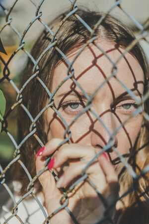 Close-up. The face of a young girl behind a metal fence Banco de Imagens