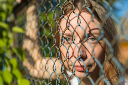 The girl in the park looks through a metal fence. 版權商用圖片