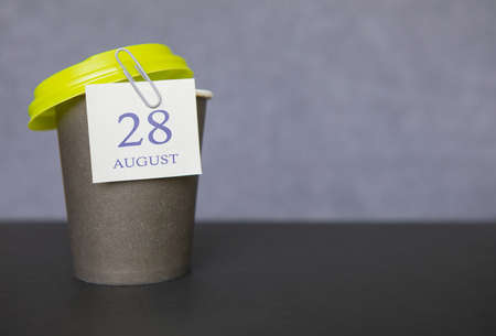 Coffee paper cup with calendar dates for August 28, summer season. Time for relaxing breaks and vacations. Standard-Bild