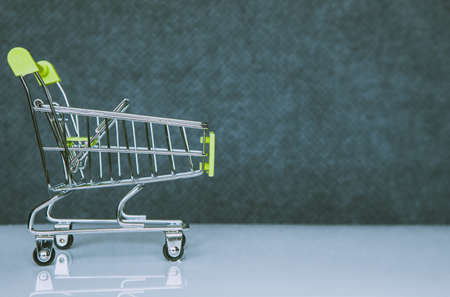 Shopping cart in green on a blurred background. Close-up. Shopping trip concept. Standard-Bild