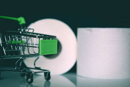 Green grocery shopping cart with Toilet Paper rolls. Concept of lack of toilet paper in stores.