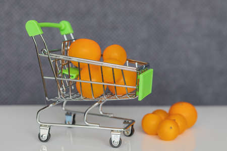 Close-up. Green shopping cart with yellow cherry tomatoes. Standard-Bild