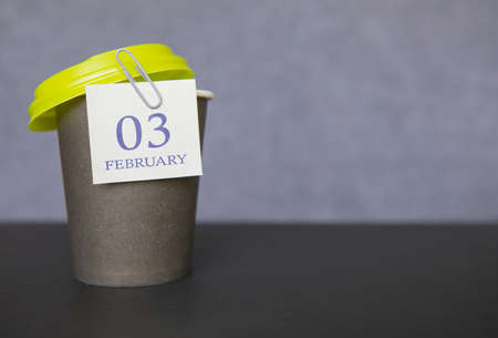 Coffee paper cup with calendar dates for February 03, Winter season. Time for relaxing breaks and vacations.