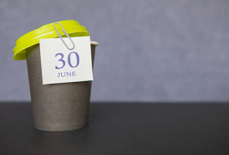 Coffee paper cup with calendar dates for June 30, Summer season. Stock Photo