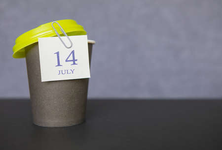 Coffee paper cup with calendar dates for July 14, Summer season. Time for relaxing breaks and vacations.