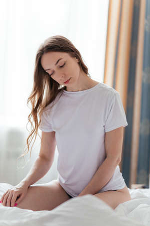 Young woman in a white T-shirt sits on a bed on a light background