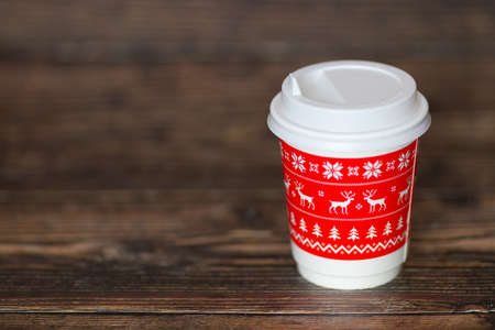 Coffee to go is on the wooden table. Christmas mood is a warm beverage. Mulled wine tea winter take away drink. Reusable zero waste mug. Blurred background.