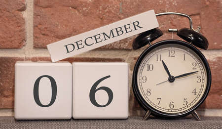 Important date, December 6, winter season. Calendar made of wood on a background of a brick wall. Retro alarm clock as a time management concept. Фото со стока