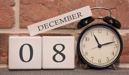 Important date, December 8, winter season. Calendar made of wood on a background of a brick wall. Retro alarm clock as a time management concept.