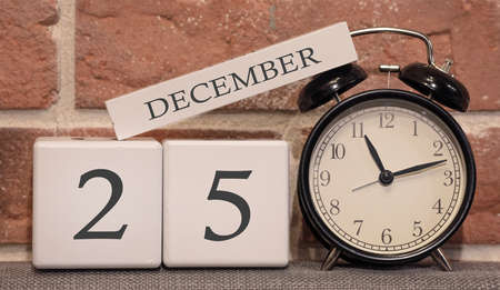 Important date, December 25, winter season. Calendar made of wood on a background of a brick wall. Retro alarm clock as a time management concept.