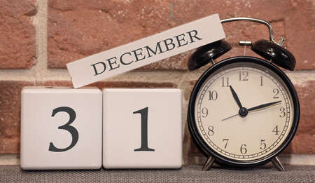 Important date, December 31, winter season. Calendar made of wood on a background of a brick wall. Retro alarm clock as a time management concept. Фото со стока