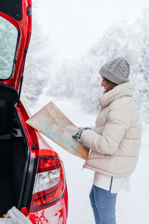 Young woman with a vintage map by the car on the background of winter forest
