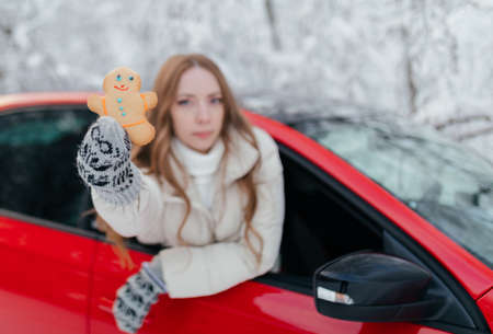 Young woman in a red car on the background of a winter forest and a little cookie