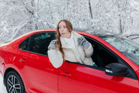 Young woman in a red car on the background of a winter forest