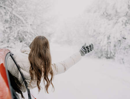 A young woman rejoices at the coming of winter. Winter forest. Фото со стока