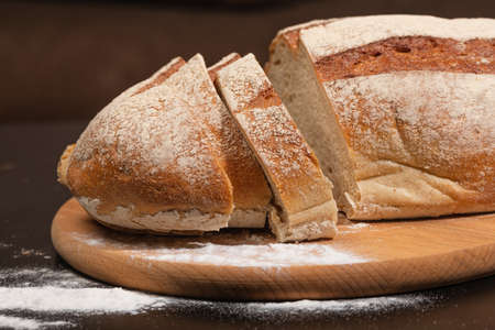 Fresh homemade baked goods. Freshly baked bread on a wooden board. Bread slices. Фото со стока