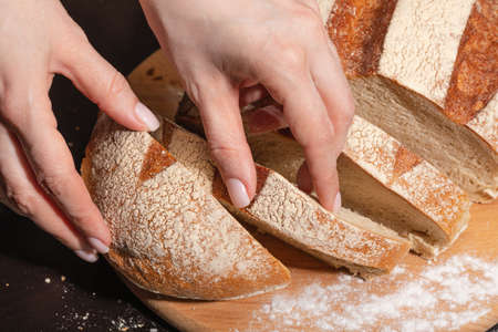 A young woman was cutting freshly baked bread into slices. Healthy eating.