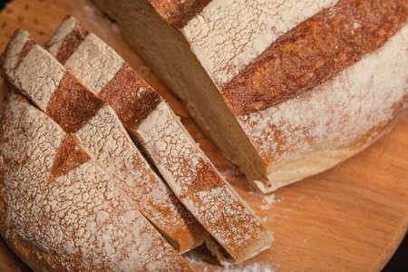 Fresh slice of bread on wooden board Фото со стока
