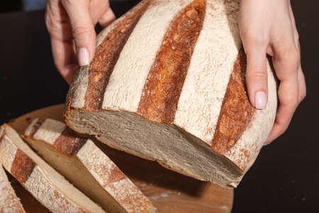 Female hands hold freshly baked bread. Homemade baking.