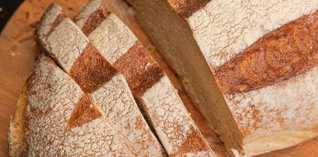 Close-up of fresh bread with slices on a wooden board. Фото со стока