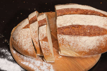 Fresh and tasty bread on a wooden board, homemade baking concept. Фото со стока