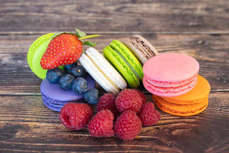 Delicious macaroons and wild berries, blueberries and raspberries on a wooden background. Фото со стока