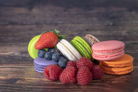 Colorful macaroons and wild berries - raspberries, blueberries stand on a wooden background. Top view with copy space Фото со стока