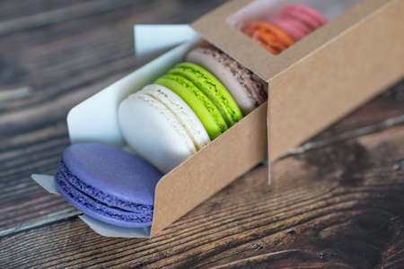 Close-up, macaroon cakes in paper box on dark background