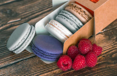 Cardboard box with macaroon cookies and raspberries, a favorite treat for children