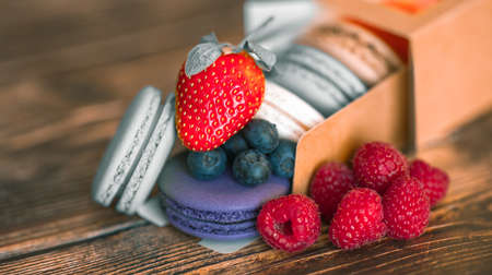 Blueberries, raspberries with strawberries on colored macaroons in a cardboard box on a wooden background