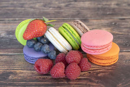 Top view. Delicious macaroons and wild berries, blueberries and raspberries on a wooden background.