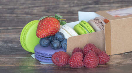 Close-up. Delicious different color macaroons and wild berries with strawberries on a wooden background. A celebration of taste.
