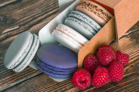 Colored macaroon and raspberry cookies in a paper box Фото со стока
