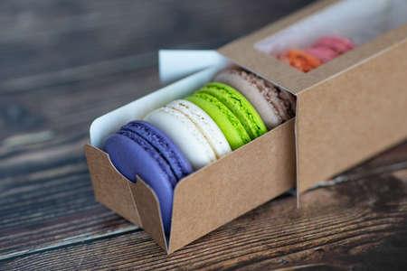 Macaroon cakes in paper box on dark background