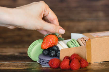 Woman's hand and macarons with fresh berries on wooden background