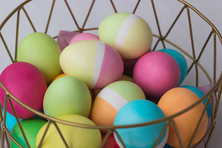 Colored Easter eggs in a basket on the table