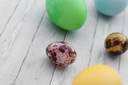 Colored Easter eggs on a light wooden background. Easter holiday with colored eggs
