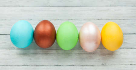 Colored Easter eggs on a light wooden background. Фото со стока