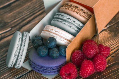 Close-up. Blueberries, raspberries and colored macaroon cookies in a cardboard box on a wooden background