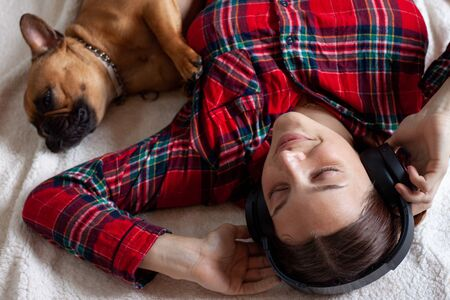 French Bulldog with young woman in headphones smiling while lying on the floor at home Stok Fotoğraf