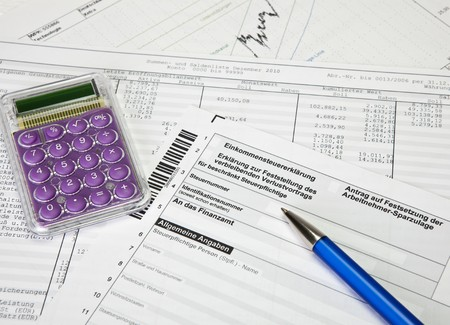 managerial: German income tax return form with calculator, charts and ballpoint pen
