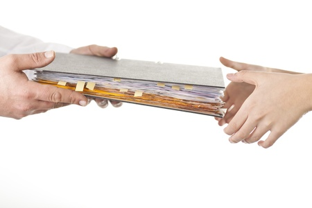 Male give file folder of paperwork to another person