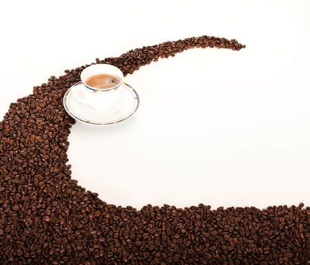 Coffe cup over coffee beans photo