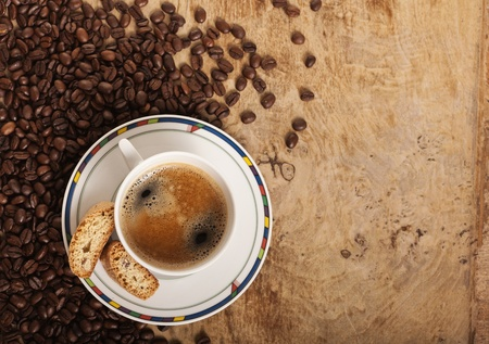 stimulated: Coffe cup over coffee beans